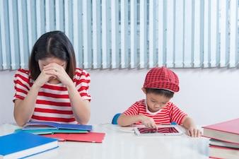 O menino asiático jogando uma mesa e sua mãe frustrada.