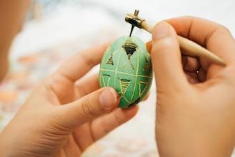 O menino corante ovo de madeira com uma cera