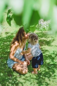 O menino está beijando sua mãe. Mamãe beija seu filho pequeno