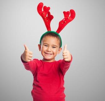 O menino feliz vestindo uma tiara de rena