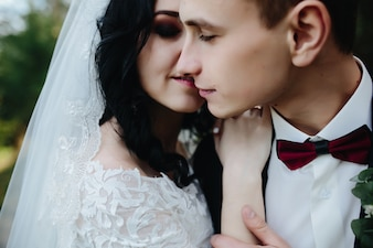 O noivo e a noiva abraçando-se de pé lá fora