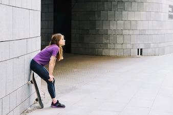 O skateboardista feminino repousa contra a parede de tijolos