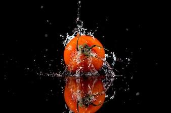 O tomate com gotas está no fundo preto