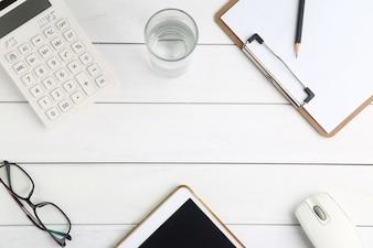 Óculos, calculadora e tablet na mesa branca e limpa