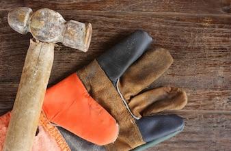 Old Hammer e luvas de couro em fundo de madeira