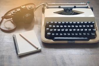 Old vintage machinewriter, film camera e caderno em branco na mesa de madeira rústica