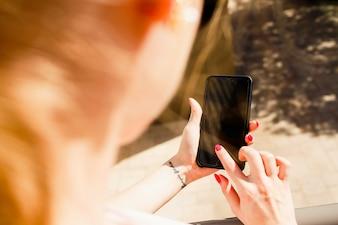 Olhe por cima do ombro da senhora no iPhone em suas mãos elegantes