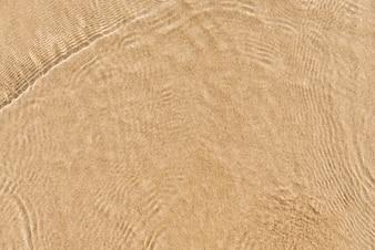 Onda suave do oceano azul na praia de areia. Fundo. Foco seletivo.