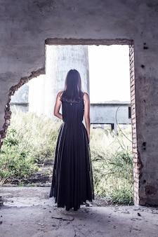 Opinião traseira a mulher usando um vestido preto