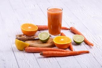 Orange Detox Coctail com laranjas, limão e cenouras fica na mesa branca