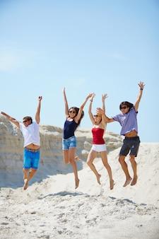 Os amigos que saltam na areia