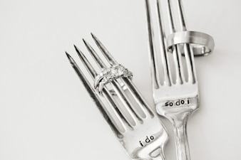 Os anéis de casamento e garfos