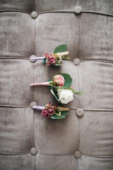 Os boutonnieres cor-de-rosa encontram-se no sofá cinza