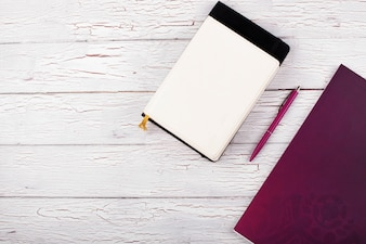 Os cadernos e caneta estão sobre a mesa
