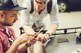 Os homens compartilham notícias, fotos, vídeos no smartphone. Um homem mostra um amigo um aplicativo em um telefone celular. Amigos com um smartphone, tecnologia.