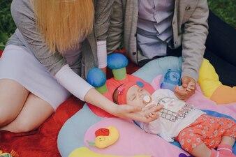 Os pais que tocam nas mãos do seu bebê
