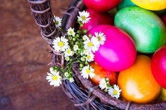 Ovos de easter coloridos na cesta marrom com flor