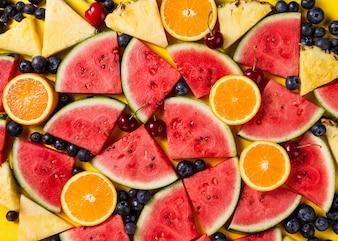 Padrão bonito com fatias de melancia fresca, abacaxi, cerejas e amoras em fundo amarelo brilhante. Vista do topo.