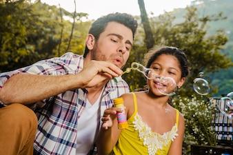 Pai e filha fazendo bolhas de sabão
