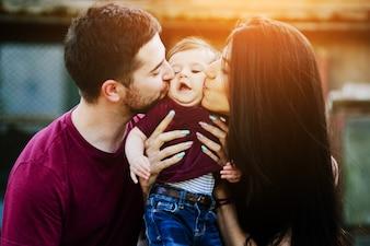 Pai e mãe beijando um bebê nas bochechas