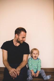 Pai olhando para seu filho ao bocejar