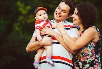 Pais alegres sorriem para o filho pequeno em seus braços