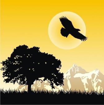 Paisagem de montanha com árvores e águia silhuetas