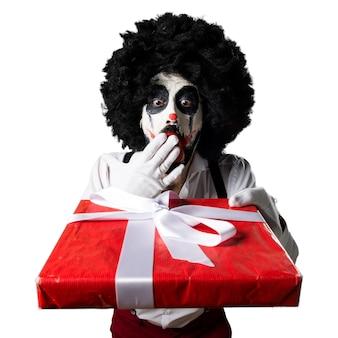 Palhaço assassino segurando um presente