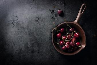Panela com cerejas em uma mesa de madeira negra, visto de cima