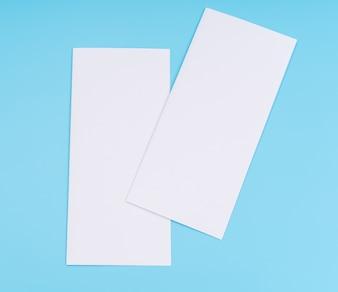 Papel branco bifold do molde no fundo azul.