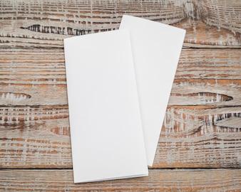 Papel branco modelo Bifold na textura de madeira.