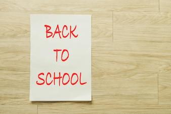 Papel de escrita com texto de volta para a escola sobre fundo de madeira.