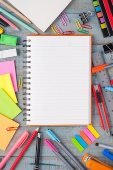 Papel para caderno e ferramentas de escola ou escritório na mesa de madeira vintage