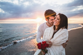 Par, andar de sorriso na praia com um buquê de rosas ao pôr do sol