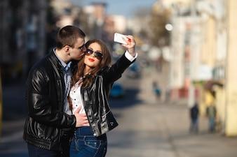 Pares no amor que toma uma foto com fundo da rua