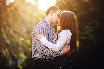 Pares novos que beijam no por do sol