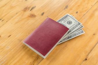 Passaporte em branco com dólares americanos em mesa de madeira.