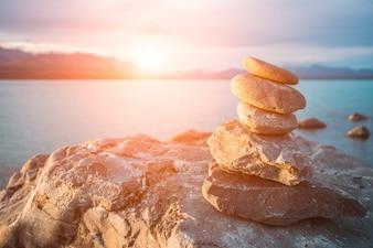 Pedras empilhadas no mar ao pôr do sol