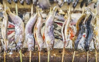 Peixe com sal que estão sendo grelhados ao ar livre no Japão