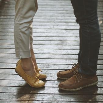 Pernas de um casal e uma mulher na ponta dos pés