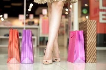 Pés de uma rapariga com sacos coloridos