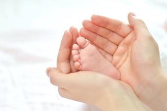 Pés do bebê nas mãos da mãe.