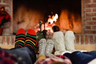 Pés em meias de Natal perto da chaminé que relaxam em casa