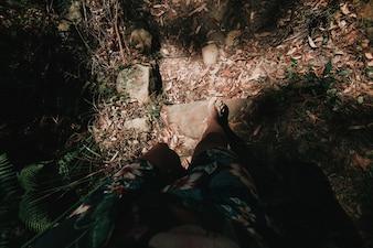 Pés masculinos andando na floresta com chinelos.
