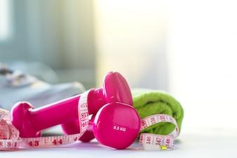 Pesos rosa, uma fita métrica e uma toalha