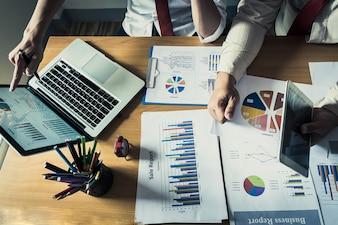Pessoa de negócios que analisa estatísticas financeiras exibidas na tela do laptop