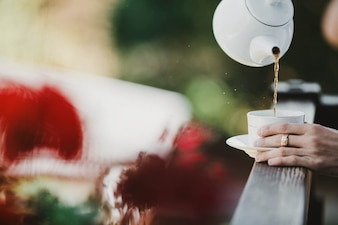 Pessoa servindo chá em uma xícara