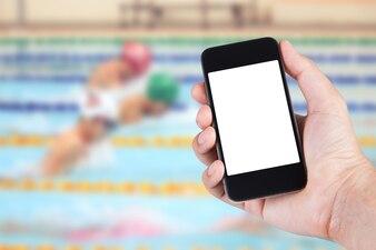 Pessoa usando o suporte de tela branca do smartphone na mão com o fundo do fundo da piscina.