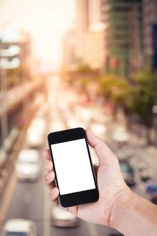 Pessoa usando o suporte de tela branca do smartphone na mão com um enxurrado de engarrafamento na rua da cidade em Bangkok, Tailândia.