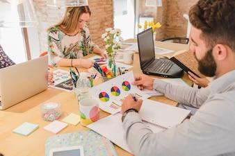 Pessoas em mesa no escritório trabalhando